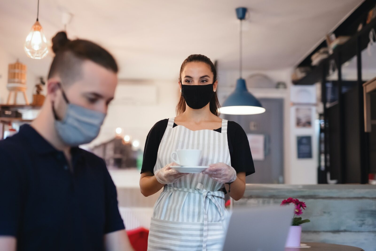 Young waitress with face mask working indoors in cafe, serving customer