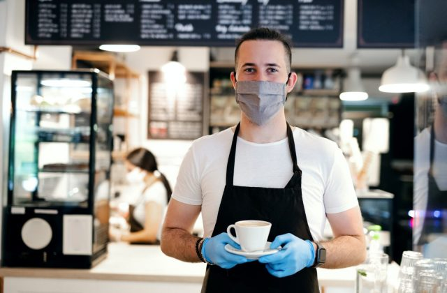 Waiter with face mask and gloves working in cafe, holding coffee